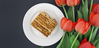 Кусок торта с гайкой на плите Букет тюльпанов Взгляд сверху Стоковое Изображение RF
