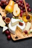 Кусок французских бри или сыра и груши камамбера на деревянной доске Стоковая Фотография