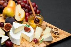 Кусок французских бри или сыра и груши камамбера на деревянной доске Стоковое Изображение RF