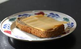 Кусок хлеба с сыром на плите в кухне стоковые изображения