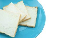 Кусок хлеба на голубой плите с белой предпосылкой Стоковое Фото