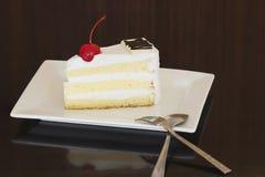 Кусок чизкейка с отбензиниванием вишни на белой плите Стоковые Изображения