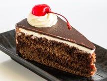Кусок шоколадного торта с вишней на сливк whipp, в мягком фокусе Стоковая Фотография
