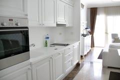 Кухня бела с белыми кухонными шкафами, плитой, холодильником, раковиной Белая комната афоризма стоковое фото