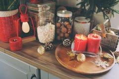 Кухня загородного дома украшенная на праздники рождества и Нового Года Marhmallows, свечи, какао и гайки в современных опарниках Стоковые Изображения
