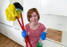 Кухня домохозяйки дома в перчатках держа веник чистки и mop и бутылку брызга Стоковое Фото