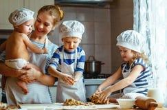 кухня семьи счастливая мать и дети подготавливая тесто, ба стоковое изображение
