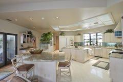 Кухня с табуретками на острове в доме Стоковое Изображение