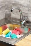 Кухонная раковина с пеной, идущей водой из крана и губками чистки Стоковое Изображение