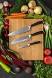 Кухонные ножи на деревянной прерывая доске с предпосылкой свежих овощей Вегетарианская сырцовая еда стоковые изображения rf