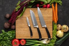 Кухонные ножи на деревянной прерывая доске с предпосылкой свежих овощей Вегетарианская сырцовая еда стоковое изображение rf