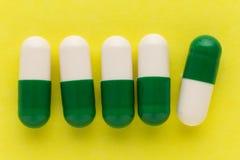 Куча белых и зеленых капсул на белой предпосылке Пилюльки Стоковая Фотография