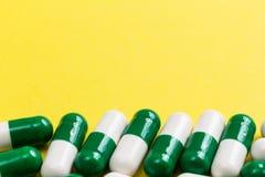 Куча белых и зеленых капсул на желтой таблице Стоковая Фотография RF