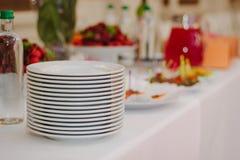 Куча белых плит на шведском столе ресторанного обслуживании Стоковое Изображение