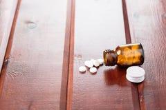 Куча белых пилюлек и стеклянной бутылки для медицин на деревянной предпосылке Стоковые Изображения RF