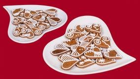 Куча богато украшенных сердец от пряника на плитах twoo белых в форме сердц Стоковое Изображение