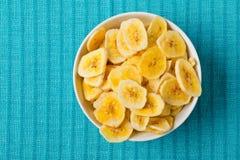 Куча высушенного банана откалывает закуску в белом шаре на голубой бирюзе Стоковые Изображения
