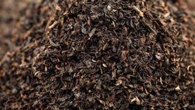 Куча высушенного урожая лист черного чая вращая близко вверх по взгляду видеоматериал