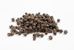 Куча высушенных перчинок черного перца изолированных на белой предпосылке Стоковые Фото