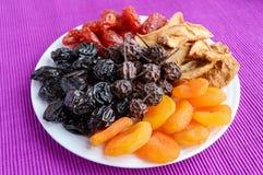 Куча высушенных яблок плодоовощей, черносливов, абрикосов, груш, клюкв на белой плите стоковые изображения
