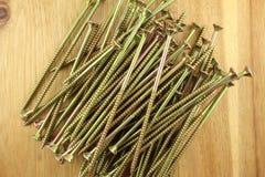 Куча деревянных винтов на деревянной доске Стоковые Фотографии RF
