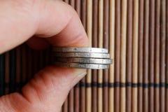 Куча евро чеканит в руке ` s человека на деревянной бамбуковой предпосылке таблицы Стоковые Изображения RF