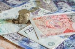 Куча денег и штабелированного gbp английских фунтов монеток стерлингового Стоковое Фото