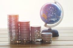 Куча денег чеканит с глобусом на таблице Стоковое Изображение RF