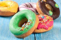 Куча застекленных donuts на голубой деревянной предпосылке Стоковое Изображение