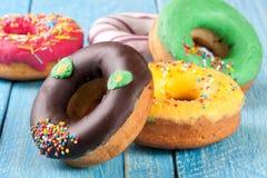 Куча застекленных donuts на голубой деревянной предпосылке Стоковая Фотография