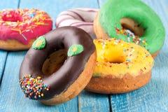 Куча застекленных donuts на голубой деревянной предпосылке Стоковые Изображения