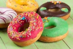 Куча застекленных donuts на зеленой деревянной предпосылке Стоковая Фотография