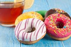Куча застекленных donuts с чашкой чаю на голубой деревянной предпосылке Стоковое Фото