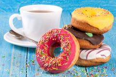 Куча застекленных donuts с чашкой чаю на голубой деревянной предпосылке Стоковая Фотография