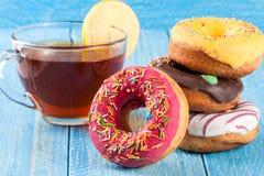 Куча застекленных donuts с чашкой чаю на голубой деревянной предпосылке Стоковое Изображение RF