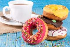 Куча застекленных donuts с чашкой чаю на голубой деревянной предпосылке Стоковое фото RF