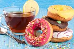 Куча застекленных donuts с чашкой чаю на голубой деревянной предпосылке Стоковые Фотографии RF