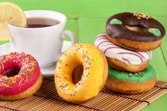 Куча застекленных donuts с чашкой чаю на зеленой деревянной предпосылке Стоковые Фотографии RF