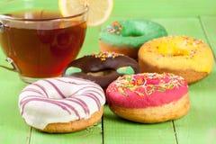 Куча застекленных donuts с чашкой чаю на зеленой деревянной предпосылке Стоковая Фотография