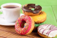 Куча застекленных donuts с чашкой чаю на зеленой деревянной предпосылке Стоковое Изображение