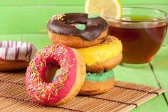 Куча застекленных donuts с чашкой чаю на зеленой деревянной предпосылке Стоковая Фотография RF
