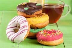 Куча застекленных donuts с чашкой чаю на зеленой деревянной предпосылке Стоковое Фото