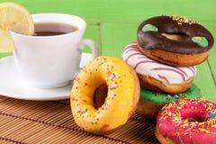 Куча застекленных donuts с чашкой чаю на зеленой деревянной предпосылке Стоковое Изображение RF