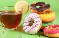 Куча застекленных donuts с чашкой чаю на зеленой деревянной предпосылке Стоковые Фото