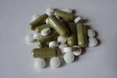 Куча зеленых капсул moringa и белых таблеток Витамина K Стоковые Фото