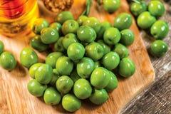 Куча зеленых оливок на таблице на деревянной доске Оливки Стоковое Изображение