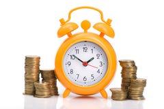 куча золотых монеток и оранжевого будильника Стоковые Фото