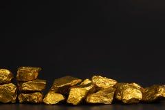 Куча золотых самородков или руда золота на черной предпосылке, драгоценный камень или шишка золотой концепции камня, финансовых и стоковые изображения