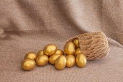 Куча золотого пасхального яйца в плетеной корзине Стоковые Изображения RF