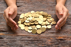 куча золотой монетки с рукой женщины на деревянном fina предпосылки Стоковая Фотография RF